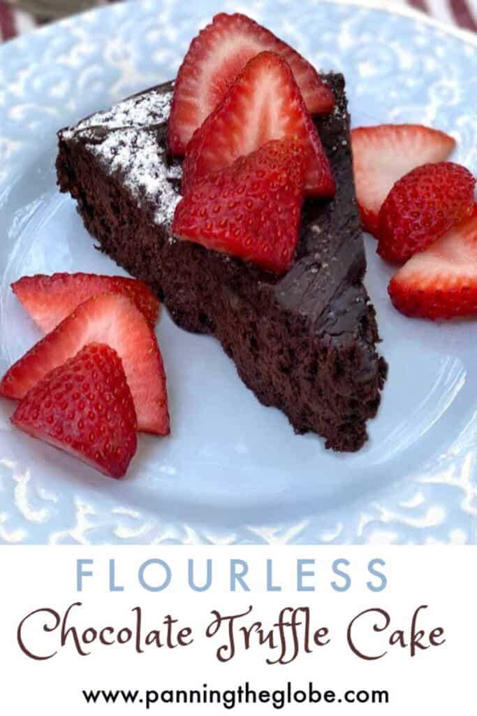 a slice of flourless chocolate truffle cake on a light blue plate, topped with sliced strawberries