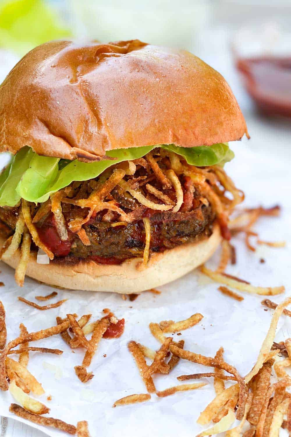 A Cuban frita burger topped with shoestring fries and a lettuce leaf, in a bun, on a piece of white parchment