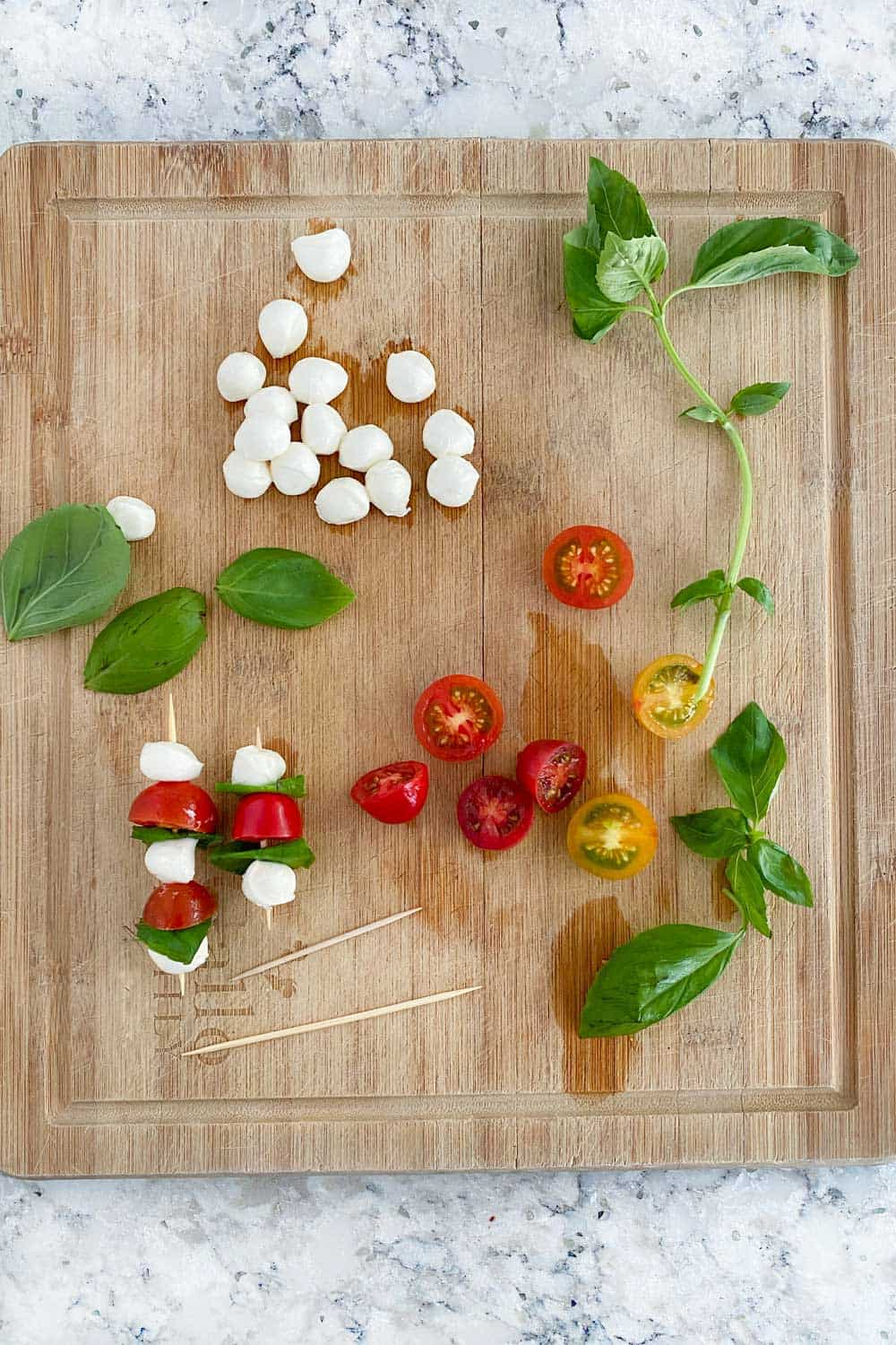 wooden cutting board with ingredients for making mini caprese skewers: a dozen mini mozzarella balls, a handful of basil leaves, a few halved cherry tomatoes and a few toothpick skewers