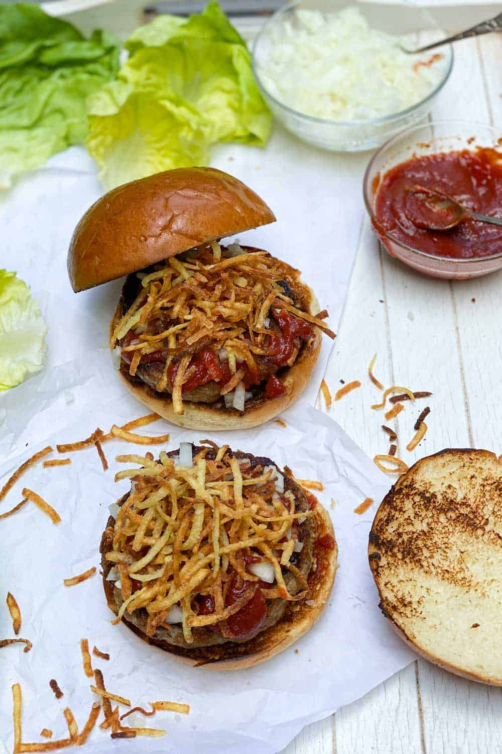 how to make the frita cuban, showing two burger patties on two buns with chopped onions and fried potatoes and special sauce on top, lettuce leaves on the side and the bun tops on the side.