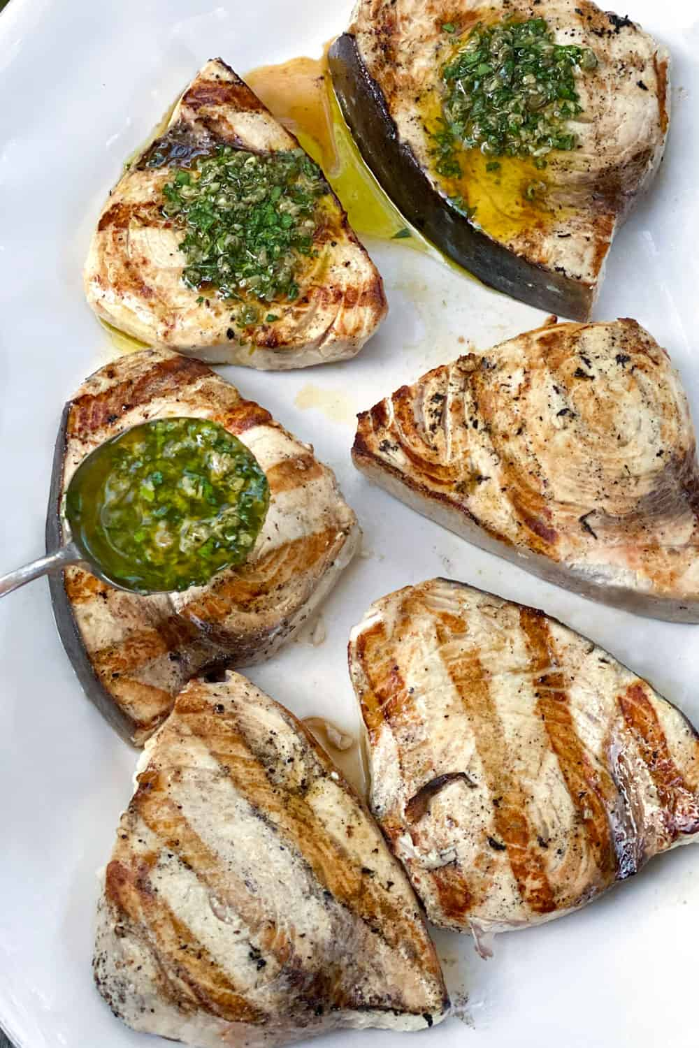 6 grilled swordfish steaks on a white platter, three are topped with salsa verde