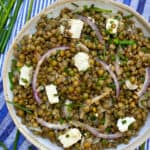 a white bowl filled with lentil salad and cubes of feta, on a blue striped dish towel with some fresh chives on the side and a couple of pink chive flowers