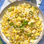 white bowl filled with sauteed corn and scallions, a blue and white striped cloth napkin underneath and several forks and a spoon on the side.
