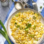 a white bowl filled with sautéed corn kernels and chopped scallions. The bowl sits on a blue and white striped cloth napkin and several pieces of flatware are in the background