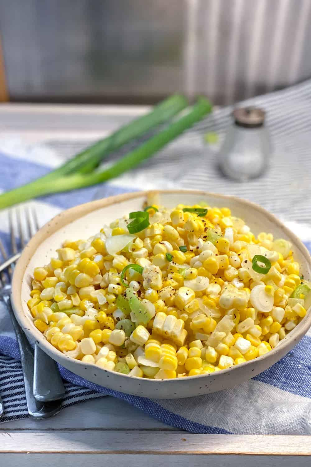 a white bowl filled with sautéed corn kernels and chopped scallions, in the background is a whole scallion and a small glass salt shaker.