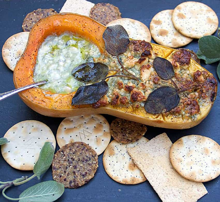 Butternut Squash half stuffed with blue cheese and topped with sage leaves, surrounded by crackers
