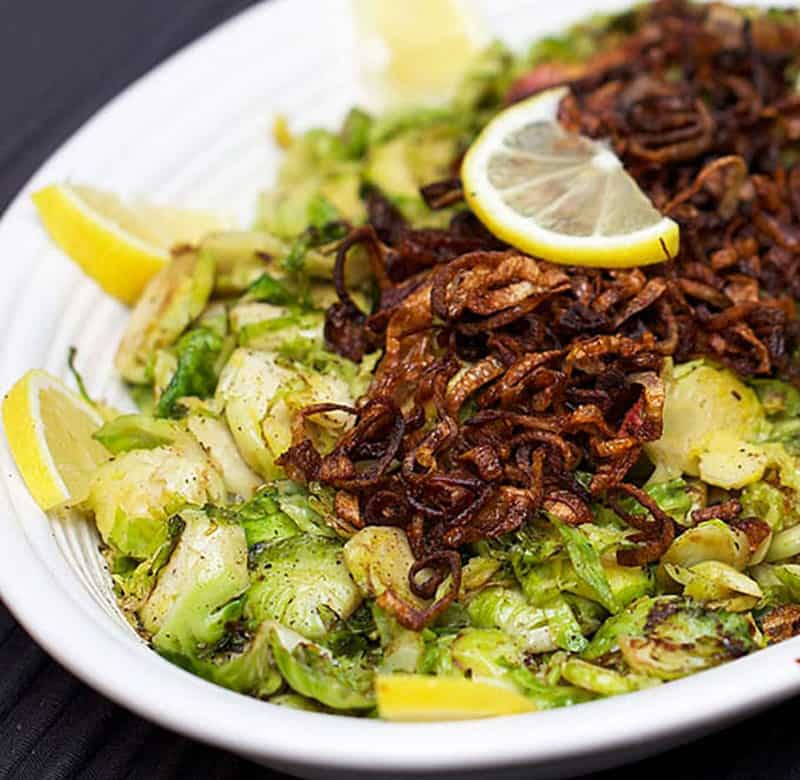 close up of a platter of shredded brussels sprouts topped with crispy fried shallots and a slice of lemon to garnish