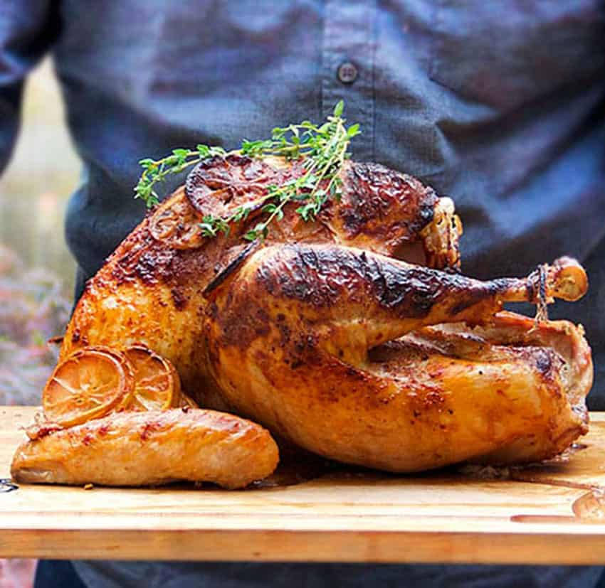 large cooked turkey on a light wooden board with a sprig of thyme on top