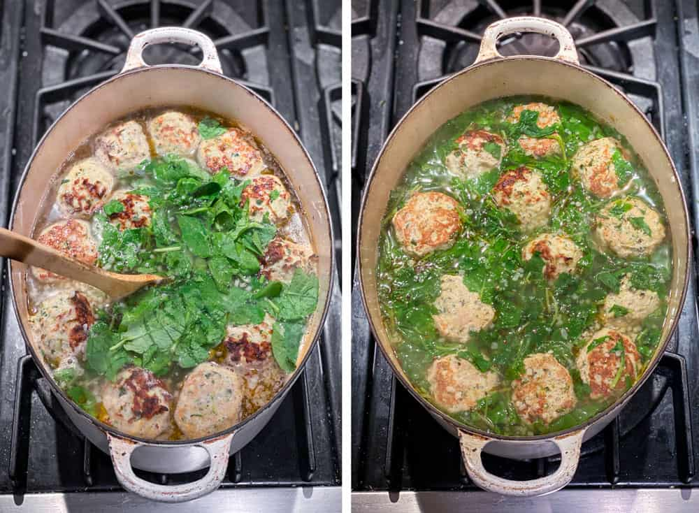 White Dutch oven seen from above as a pile of raw spinach is added to a pot of Italian wedding soup that's loaded with meatballs