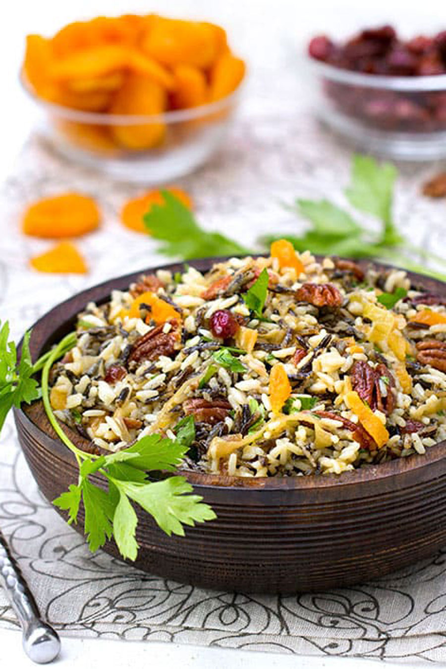 wild rice salad in a brown wooden bowl with a small bowl of dried apricots and a small bowl of dried cranberries in the background