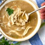 Creamy chicken soup with lots of shredded chicken in a white bowl with a leaf of parsley and a spoon