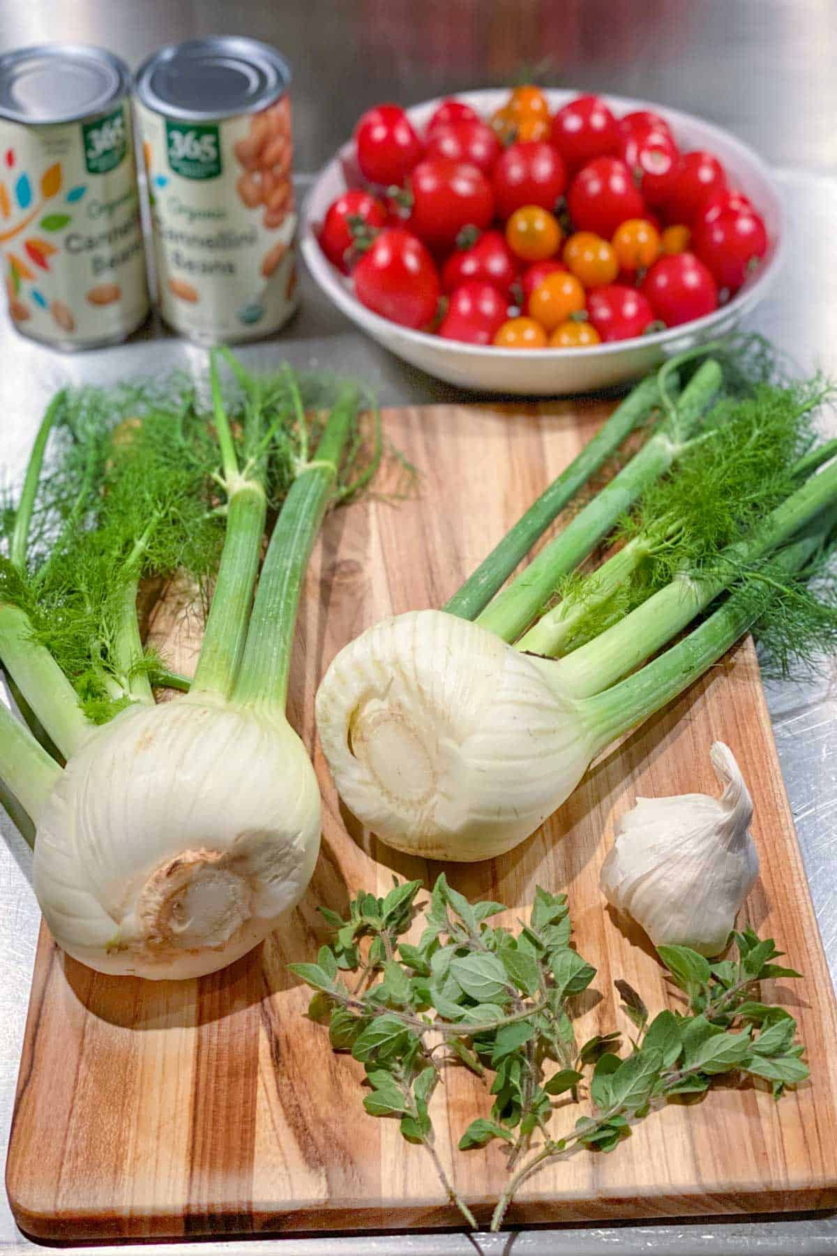 two whole fennel bulbs with fronds on a wooden cutting board with a whole bulb of garlic and several sprigs of fresh oregano, a bowl of cherry tomatoes and two cans of white beans in the background