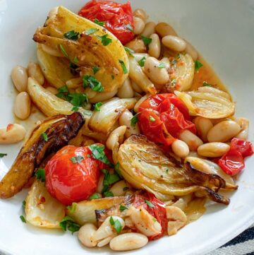 white bowl filled with roasted fennel, tomatoes and white beans