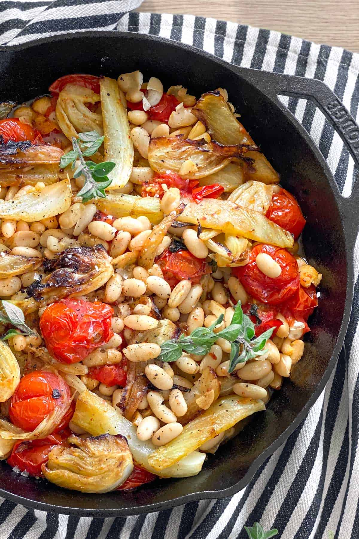 close up looking down into a cast iron skillet filled with roasted fennel, tomatoes and white beans, all set on a black and white striped dish towel.
