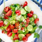 A white bowl filled with Shirazi salad of cucumbers cherry tomatoes green peppers and onions