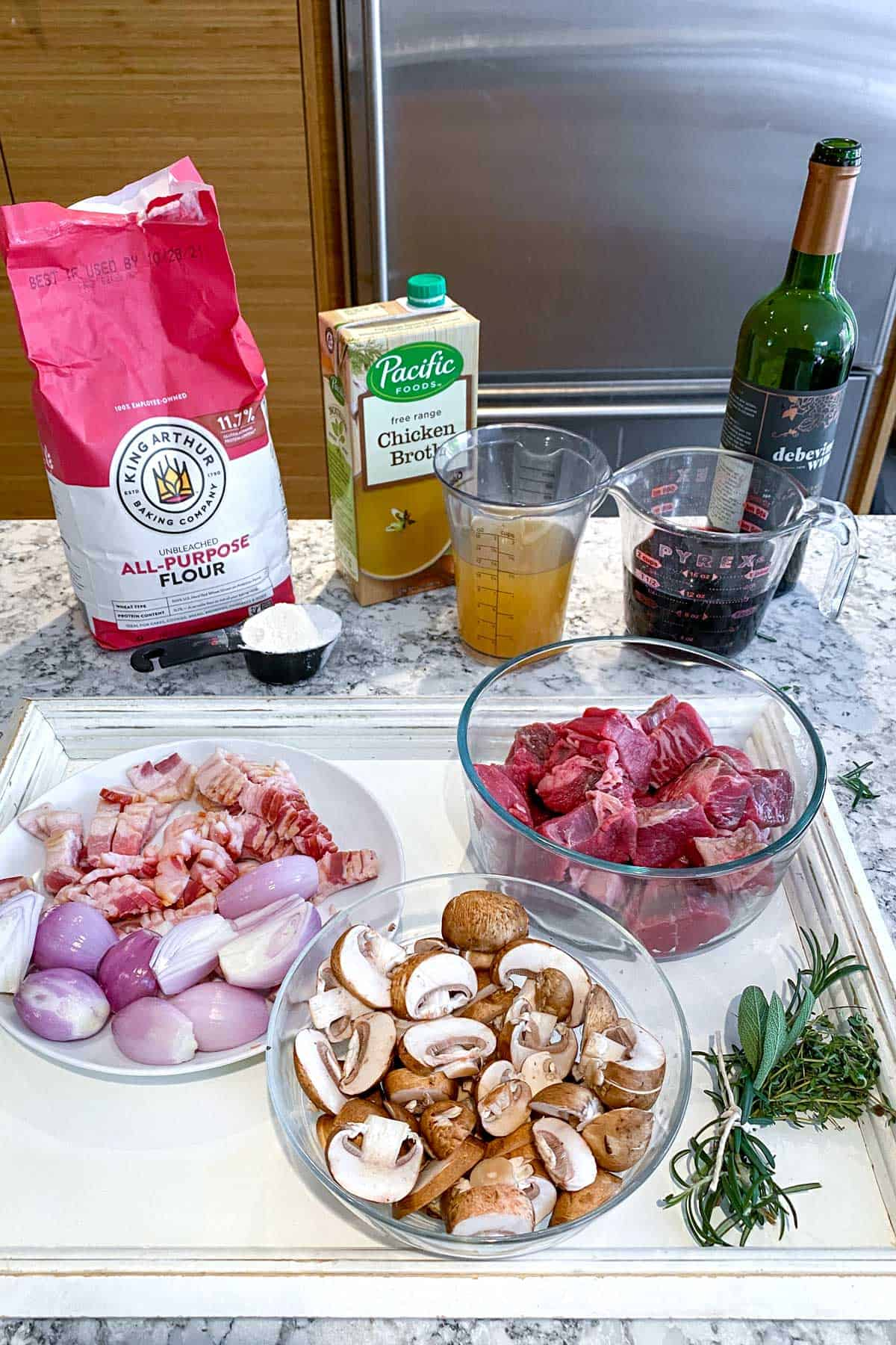 Ingredients for beef bourguignon on a white countertop: a bag of flour, glass bowl with cubed beef, bowl of sliced mushrooms, plate with chopped bacon and shallots, chicken broth in a clear cup, red wine in a clear cup, flour in a small black cup and herbs tied together