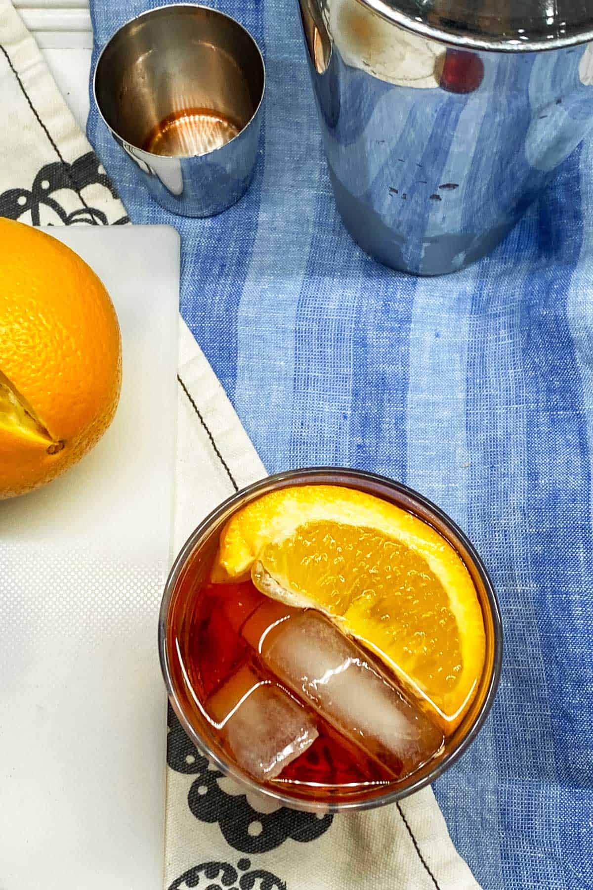 looking down into a negroni cocktail with ice and an orange slice, on a blue dish towel