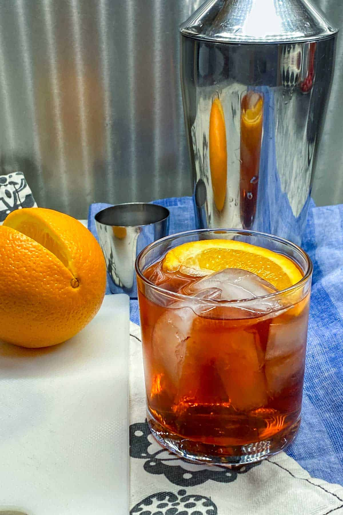 negroni cocktail in the foreground with an orange slice as a garnish, an orange and a cocktail shaker in the background