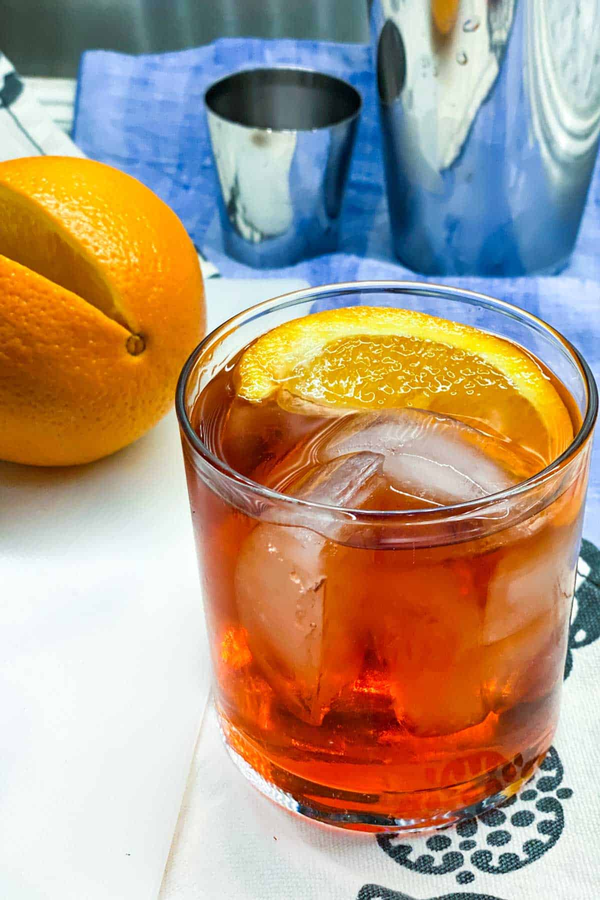 close up of a negroni cocktail in a glass with ice and an orange slice garnish, an orange and a cocktail shaker in the background, on a blue dish towel
