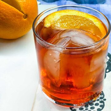 close up of a Negroni in a tumbler with ice and an orange wedge