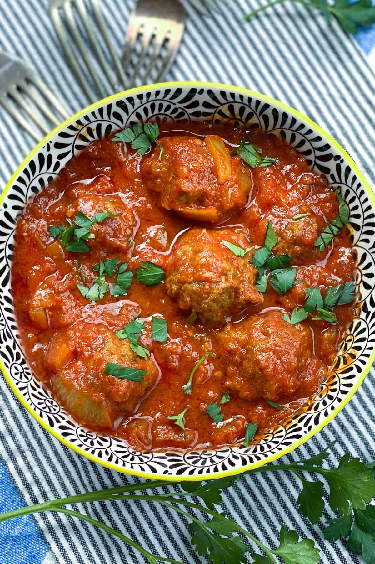 black and white decorative bowl filled with 6 Moroccan meatballs in tomato sauce, with chopped parsley sprinkled on top and a few forks in the background