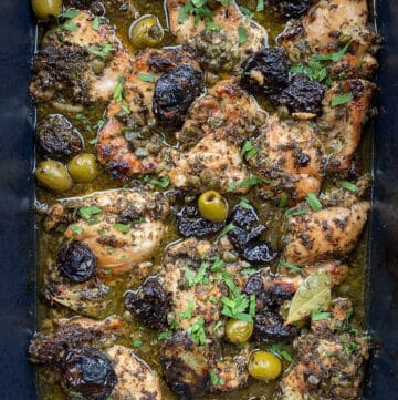 10 pieces of chicken Marbella in a roasting pan with prunes, green olives and a garnish of chopped parsley