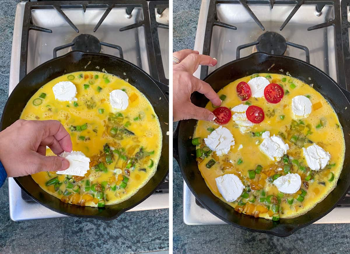 Cast iron skillet filled with sautéed chopped asparagus and whisked eggs, with 3 rounds of goat cheese being added by hand, the next shot shows the skillet filled with 8 rounds of goat cheese over the eggs, and slices of cherry tomato are being added on top.