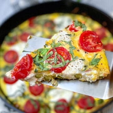 A slice of an asparagus goat cheese frittata with cherry tomatoes, on a spatula, held over the cast iron skillet containing the rest of the frittata