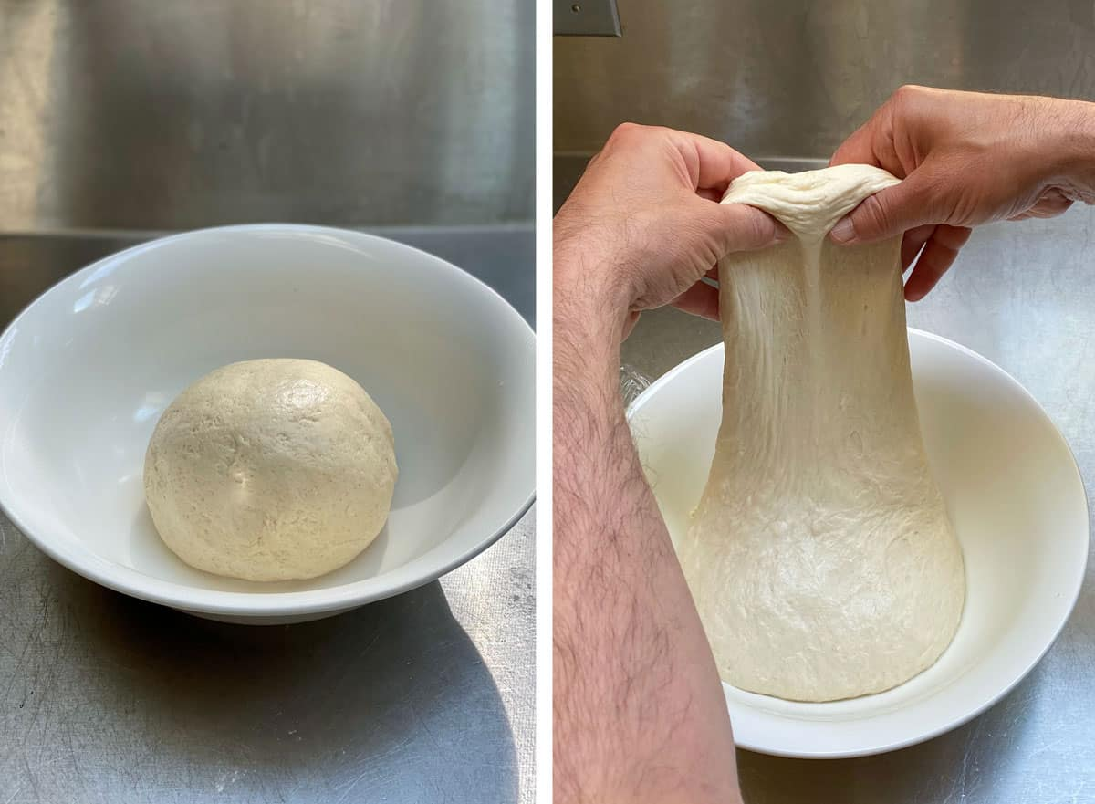 Ball of bialy dough in a white dough bowl, hands stretching the dough to demonstrate the stretch and fold technique