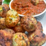 a pile of turkey corn meatballs on a white plate with a small bowl of red pepper dipping sauce in the background