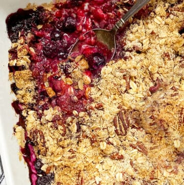 close up of a white baking pan filled with a mixed berry crumble, a spoon sticking out of the fruit
