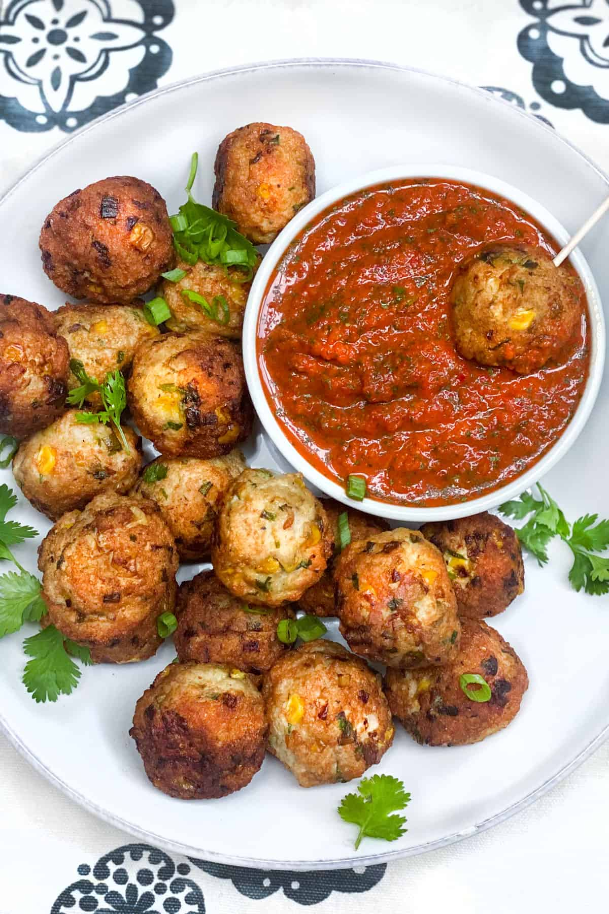 16 turkey corn meatballs on a plate surrounding a small bowl of roasted red pepper sauce, with one meatballs on a toothpick, resting in the sauce
