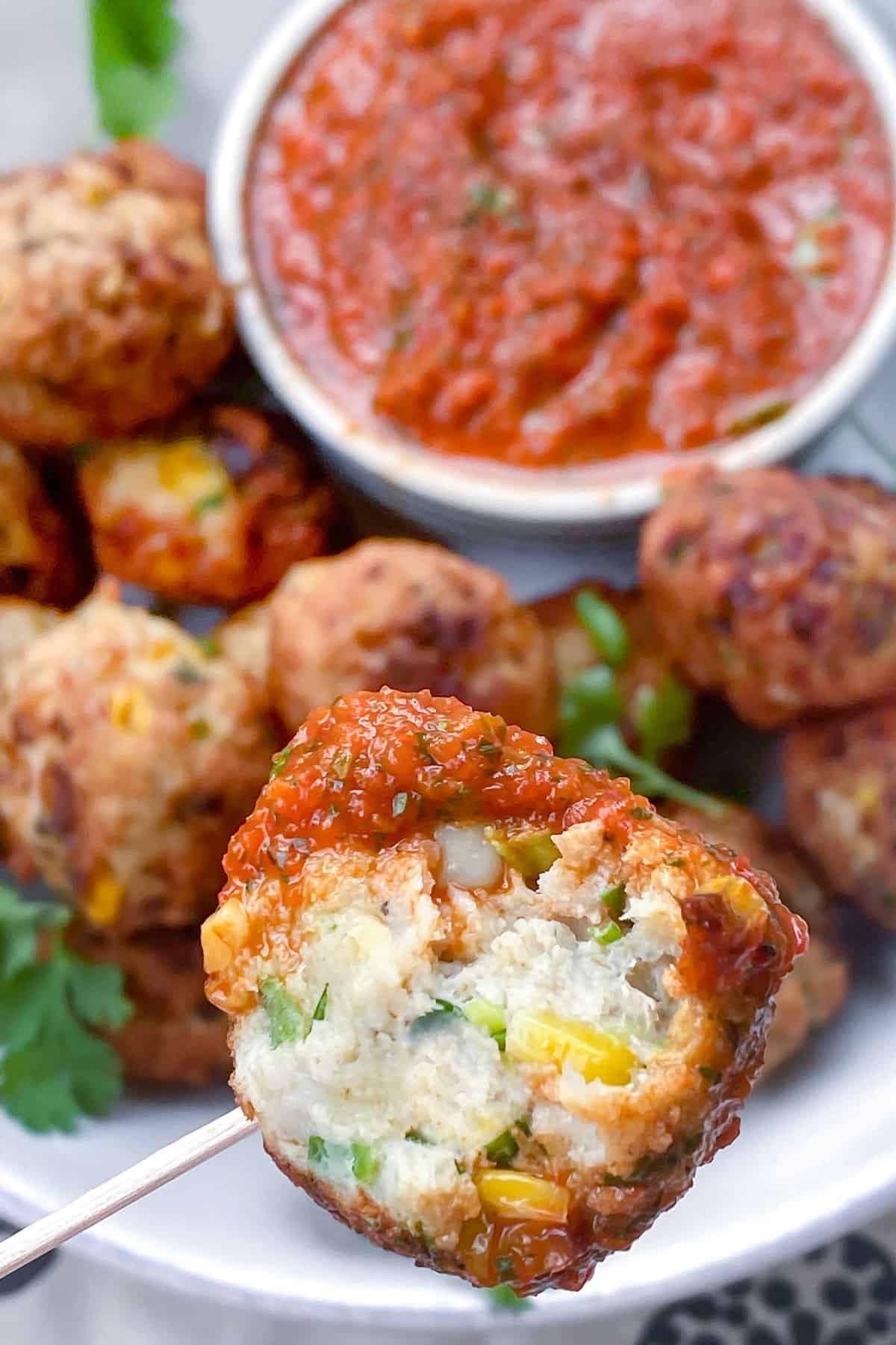 Close up of a turkey corn meatball with a bite take out of it, the platter of meatballs and red pepper sauce in the background