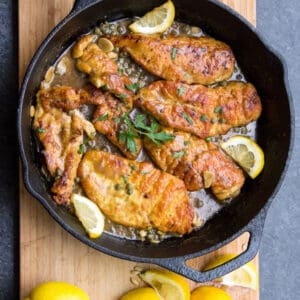 7 pieces of boneless chicken piccata in a cast iron skillet with capers, slices of lemon and a sprig of parsley