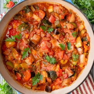 a Dutch oven filled with colorful ratatouille, a few sprigs of parsley strewn around.