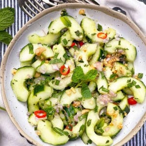 a white speckled bowl filled with thai cucumber salad.