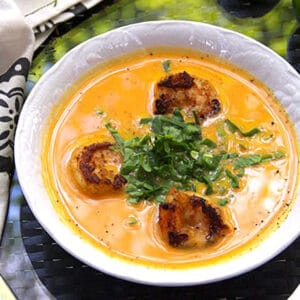 a white bowl filled with creamy orange sweet potato soup topped with three spice crusted shrimp and slivered spinach in the middle