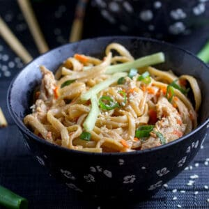 a black bowl filled with Chinese sesame noodles with chicken.