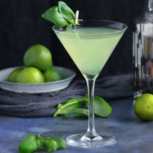 green tinted basil vodka gimlet in a martini glass with a sprig of basil clipped onto the top of the glass with a mini clothespin, a bowl of limes in the background