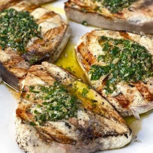 three grilled swordfish steaks topped with salsa verde