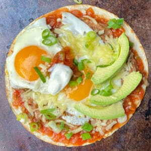 flour tortilla topped with refried beans, salsa, two fried eggs, sliced avocado, melted cheese and chopped scallions.
