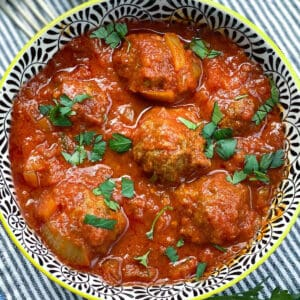 moroccan meatballs in a black and white patterned bowl, sprinkled with chopped parsley