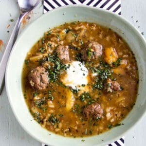 light green bowl filled with Persian meatball soup, a dollop of sour cream in the middle
