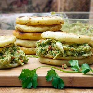 two Venezuelan arepas stuffed with avocado chicken salad and a stack of 5 arepas in the background