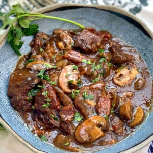 A blue bowl filled with beef bourguignon, a spring of parsley on the side