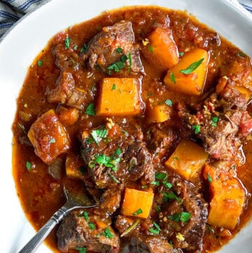 A white bowl of beef short ribs stew with butternut squash and a sprig of parsley