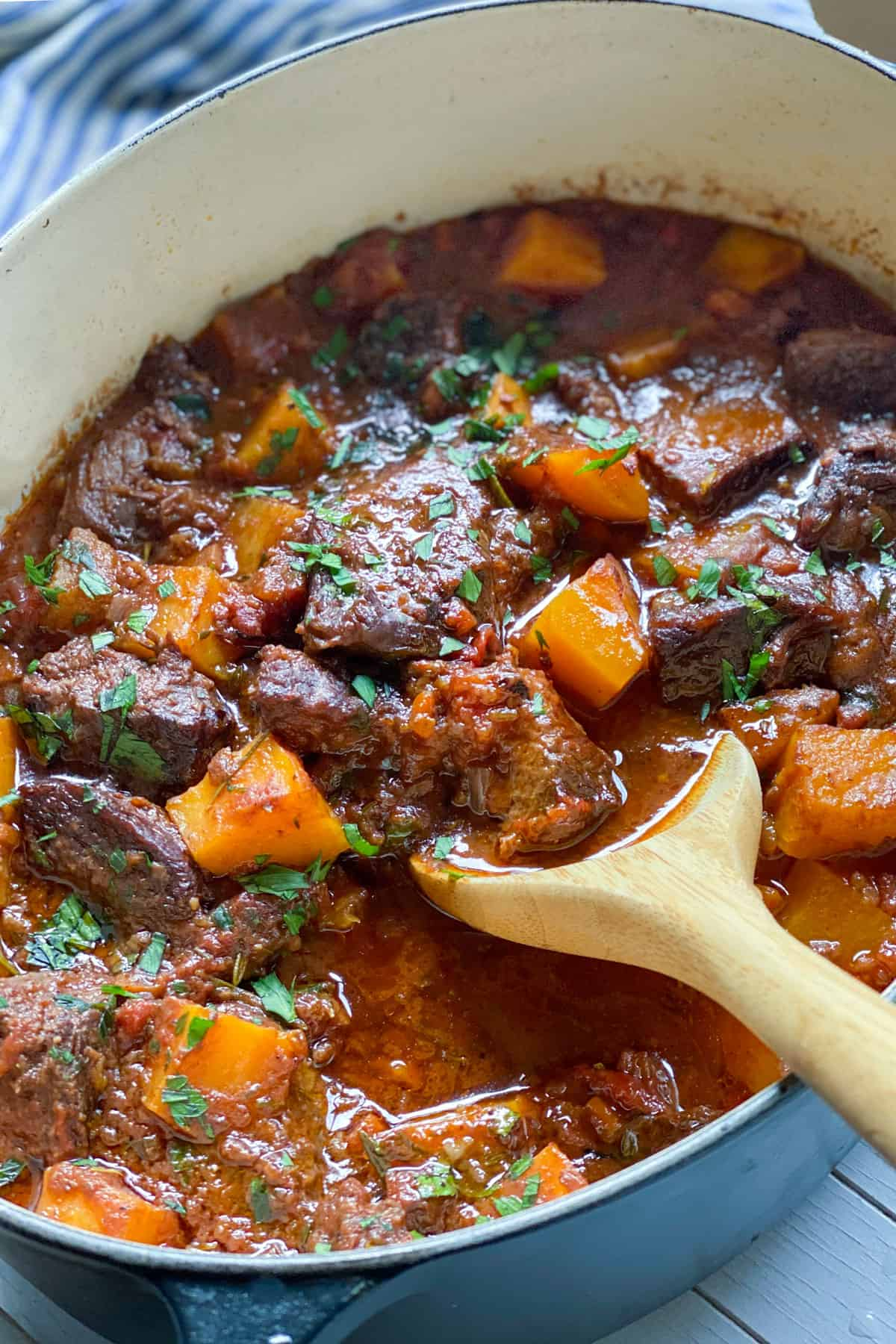 A dutch oven filled with a stew of beef short ribs and cubed butternut squash